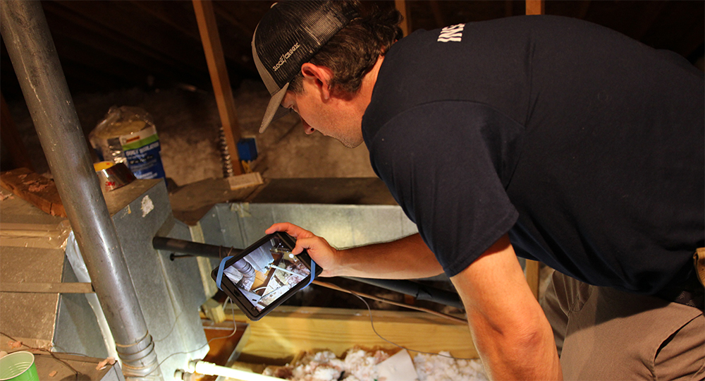 Crawford, one of our home inspectors, inspecting the attic of a house