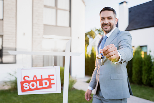 Real estate agent handing over the keys to a house sold after passing home inspection services